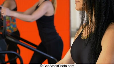 Group of women exercising on treadmill and doing cardio training at fitness studio and wearing smartwatch