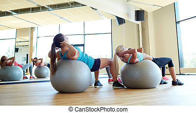 group of women exercising with fit balls in gym