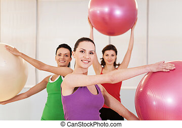 Group of women in pilates class at gym. beautiful girls holding balls and smiling