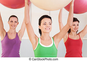 Group of women in pilates class at gym. beautiful girls lifted balls and smiling