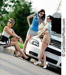 Group of women near the broken car on the road