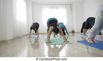Group of women practicing warrior yoga pose and meditating...