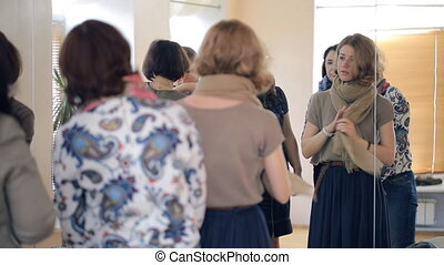 Group of women stands in front of the mirror talking to each other