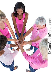 Group of women wearing pink and ribbons for breast cancer putting hands together on white background