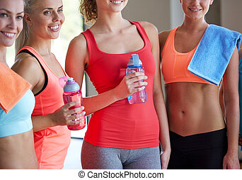 group of women with water bottles  in gym