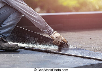 Asia worker installing tar foil on the rooftop of building. Waterproof system by gas and fire torching