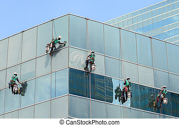 group of workers cleaning windows service on high rise building
