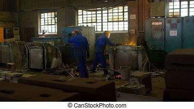 Group of workers heating molten metal in workshop 4k