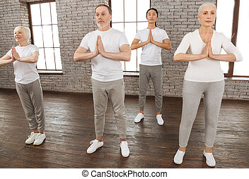 Group of yoga lovers while doing exercises