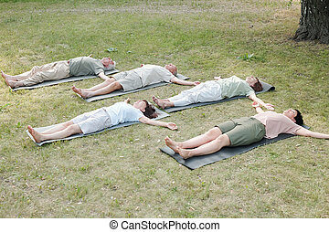 Group of yoga students lying in corpse pose - Group of ...