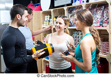 Group of young adults discussing bodybuilding supplements