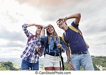 group of young adults looks to the horizon during hiking