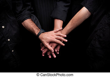 Group of young adults making a pile of hands