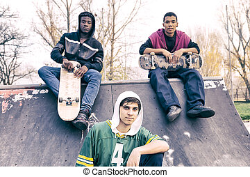 group of young adults sitting on a ramp with skateboard