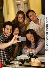 Group of young adults taking a selfie photo in a restaurant