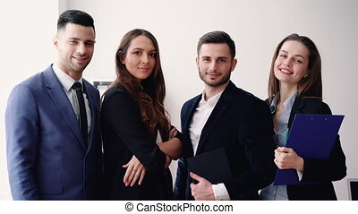 Group of young and smiling business people in modern office