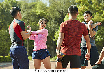 group of young asian athletes stretching legs and arms