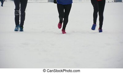 Group of young athletes running on snow, focus on its feet