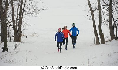 Group of young athletes running technically in winter forest