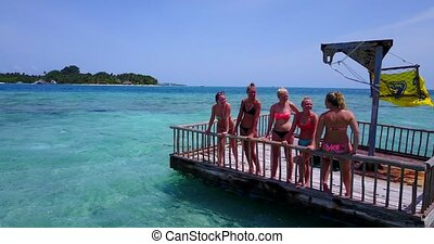 group of young beautiful girls sunbathing on pontoon with...