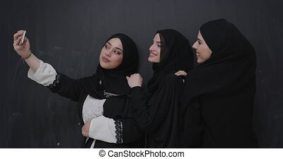 Muslim women group in a fashionable dress with hijab using smartphone over chalkboard background and taking selfie photo