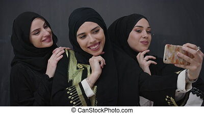Beautiful Muslim women in fashionable dress with hijab using mobile phone over chalkboard background
