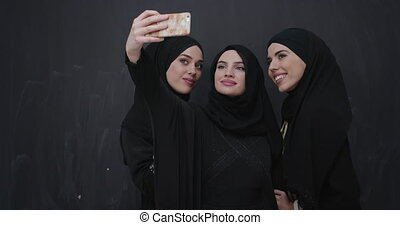 Beautiful muslim women in fashionable dress with hijab using mobile phone over chalkboard backgorund