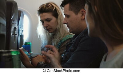 Group of young beautiful people sitting on the plane near...