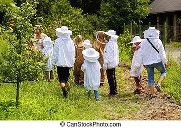 Group of young beekeepers are about to visit beehives.