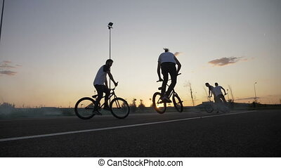 Group of young bikers friends hanging and riding on smoky...