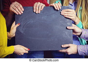 Group of young business partners with blank blackboard sign