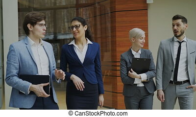 Group of young business people talking and walking in office lobby