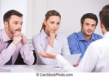 Group of young business people talking on business meeting. over shoulder view of man sitting at meeting in office