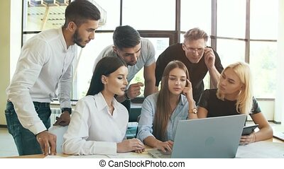 Group of young businessmen working with laptop together