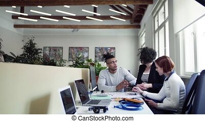 A group of young businesspeople talking in office, start-up concept.