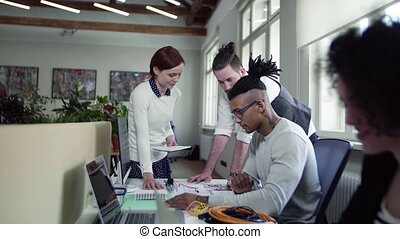 Group of young businesspeople talking in office, start-up...