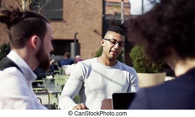 Group of young businesspeople using laptop outdoors in cafe, start-up concept.