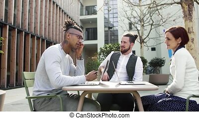 Group of young businesspeople using laptop outdoors in courtyard, start-up concept.