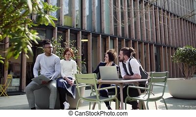Group of young businesspeople using laptop outdoors in...