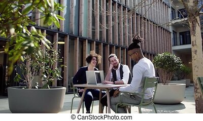 A group of young businesspeople with laptop in outdoor cafe, talking. A start-up concept.