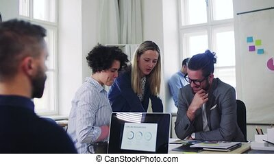 Group of young businesspeople with laptop working together...