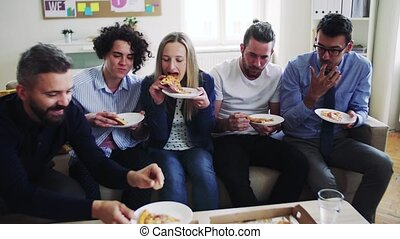 Group of young businesspeople with pizza having lunch in a...