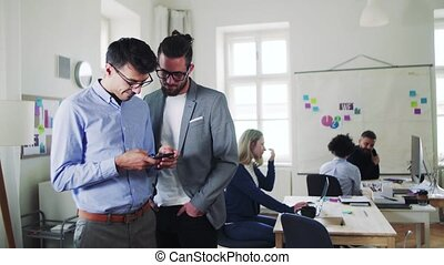 Group of young businesspeople with smartphone working...