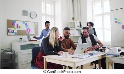 Group of young businesspeople working together in office,...