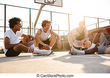Group of young cheerful multiethnic men basketball players ...