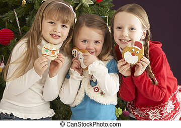 Group Of Young Children With Presents In Front Of Christmas Tree