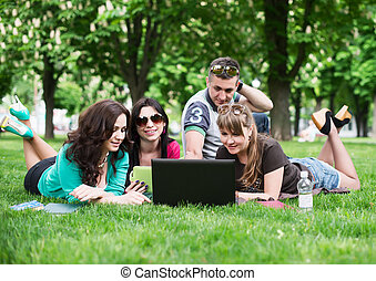 Group of young college students sitting on grass