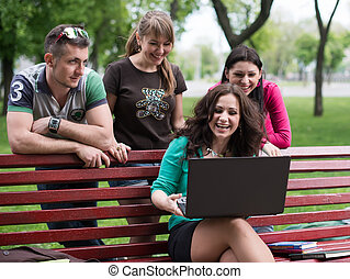 Group of young college students using laptop