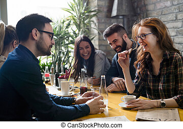 Group of young coworkers socializing in restaurant - Picture...