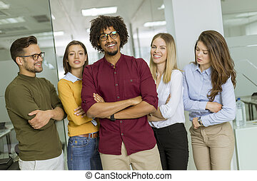 Group of young excited business people standing in office